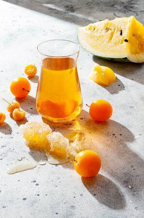 Refreshing peach ice tea or lemonade in glasses. Summer yellow fruit cocktail. Hard light harsh shadows.