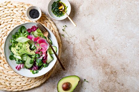Mix fresh leaves salad with lamb's lettuce, avocado, cucumber, watermelon radish, seeds and sprouts. Overhead view, copy space