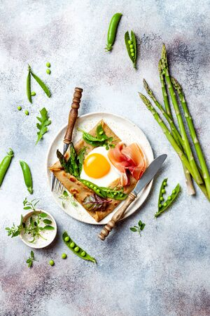 Buckwheat crepes, galette bretonne with asparagus, egg, green pea, jambon or prosciutto. Galette sarrasin, french brittany cuisine