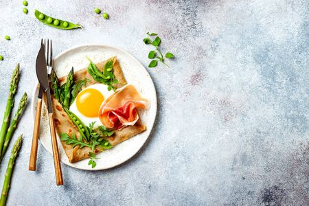Buckwheat crepes, galette bretonne with asparagus, egg, green pea, jambon or prosciutto. Galette sarrasin, french brittany cuisine 版權商用圖片 - 148223586