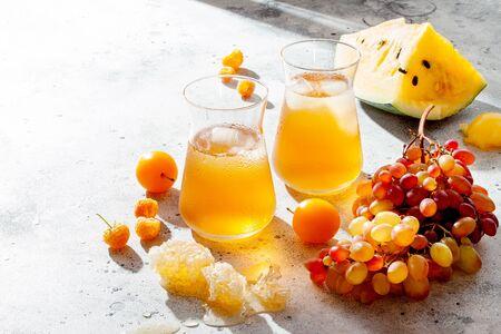 Refreshing peach ice tea or lemonade in glasses. Summer yellow fruit cocktail. Hard light harsh shadows. 版權商用圖片