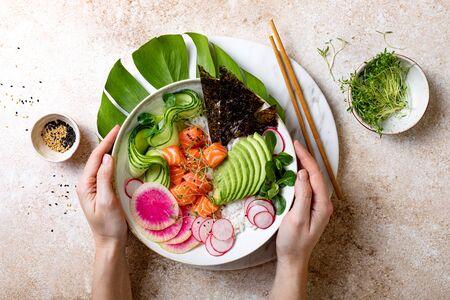 Girl holding Hawaiian salmon poke bowl with seaweed, avocado, watermelon radish and cucumber. Top view, overhead, flat lay