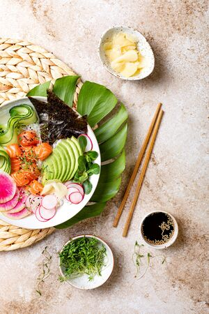 Hawaiian salmon poke bowl with seaweed, avocado, watermelon radish and cucumber. Top view, overhead, flat lay