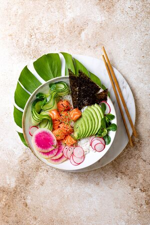 Hawaiian salmon poke bowl with seaweed, avocado, watermelon radish and cucumber. Top view, overhead, flat lay 版權商用圖片 - 148223020