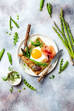 Buckwheat crepes, galette bretonne with asparagus, egg, green pea, jambon or prosciutto. Galette sarrasin, french brittany cuisine 版權商用圖片 - 148223024