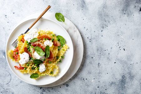 Italian pasta mafalde with green peas, prosciutto, burrata,  and spinach 版權商用圖片 - 148222597