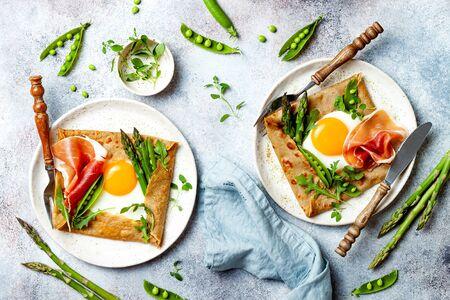 Buckwheat crepes, galette bretonne with asparagus, egg, green pea, jambon or prosciutto. Galette sarrasin, french brittany cuisine Archivio Fotografico