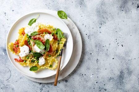 Italian pasta mafalde with green peas, prosciutto, burrata,  and spinach
