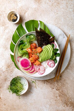 Hawaiian salmon poke bowl with seaweed, avocado, watermelon radish and cucumber. Top view, overhead, flat lay