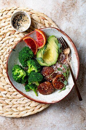 Vegan tempeh buddha bowl. Marinated tempeh in smoky bbq sauce marinade or teryaki tempeh with rice, steamed broccoli, avocado, blood orange and micro greens.