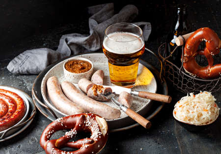 Oktoberfest beer with grilled weisswurst white sausages, bavarian pretzels and mustard sauce. Ideas, recipes how to celebrate the beer festival 2020 at home