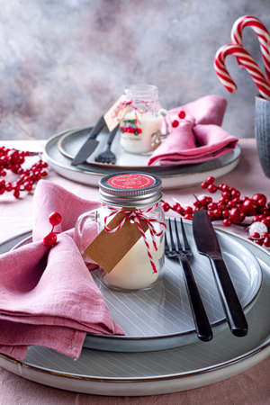 Festive Christmas and New Year celebration party table setting. Table served for Christmas dinner and decorated with candy canes, red berries and candles. 版權商用圖片