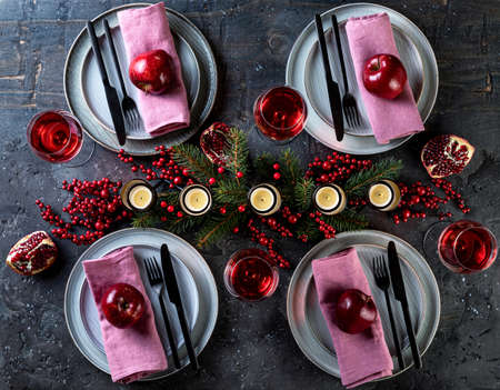 Festive Christmas and New Year celebration party table setting. Table served for Christmas dinner and decorated with branches, red berries and candles