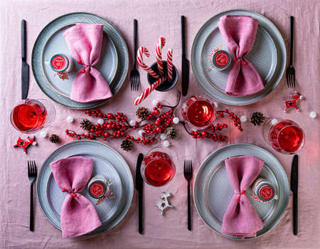 Festive Christmas and New Year celebration party table setting. Table served for Christmas dinner and decorated with pine cones, red berries and candles