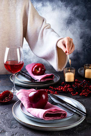 Woman lighting candles on decorated table at Christmas. Festive Christmas and New Year celebration party table setting. Table served for xmas dinner and decorated with branches, red apples, berries and candles 版權商用圖片