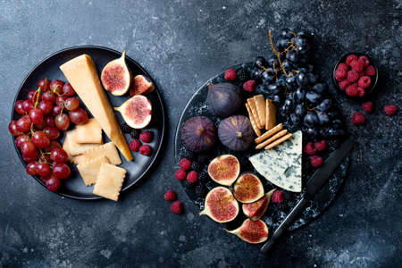 Appetizers, antipasti snacks and wine in glasses. Cheese and fruit platter on marble board over black background. Top view 版權商用圖片