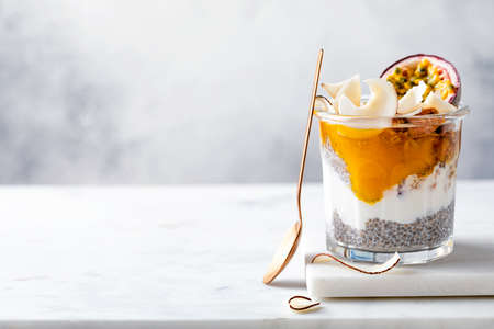 Healthy tropical fruit chia pudding with granola, mango, passion fruit and coconut chips in a glass jar. Vegan healthy breakfast, clean eating.