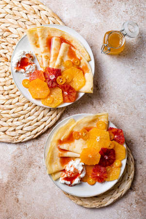Homemade crepes pancakes with ricotta and fresh oranges. French Crepe Suzette with bloody oranges syrup.