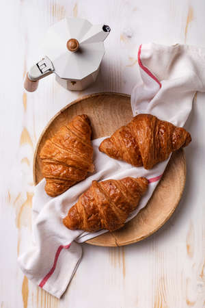 Freshly baked croissants on white wooden table. Morning French continental breakfast with fresh growing.