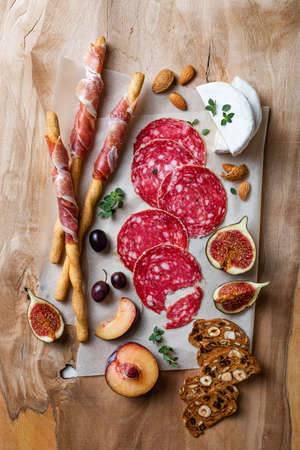 Appetizers table with italian antipasti snacks. Brushetta or authentic traditional spanish tapas set, cheese and meat variety board over wooden background. Top view, flat lay 版權商用圖片