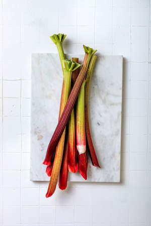 Fresh organic red rhubarb on white marble board. Bunch of fresh picked rhubarb stalks. Top view, copy space.