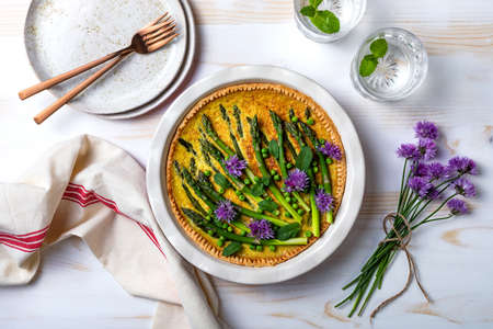 Green asparagus, sweet peas Tart with edible chives flowers or blossoms. Seasonal spring dinner table, overhead view.