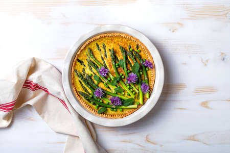 Green asparagus, sweet peas Tart with edible chives flowers or blossoms. Seasonal spring dinner, overhead view.