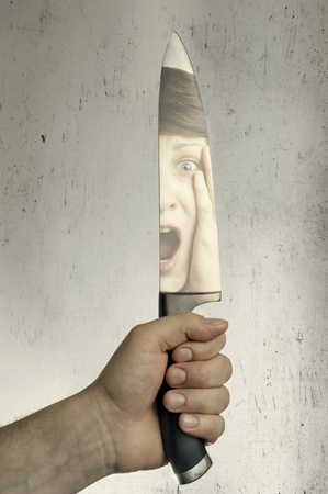 reflection: image of a hand with a large knife, a reflection of the face of the victim in the blade
