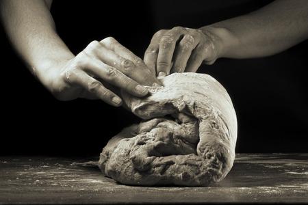 Les mains des femmes pétrissent la pâte sur un fond noir