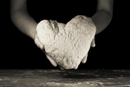 Vrouwelijke handen houden het deeg in de vorm van het hart