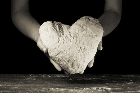 female hands hold the dough in the shape of heart Standard-Bild