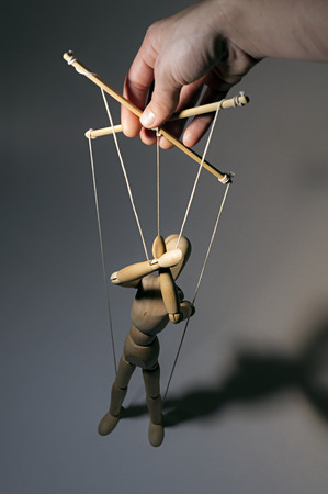 puppet master: Hand manipulating a puppet on a dark background