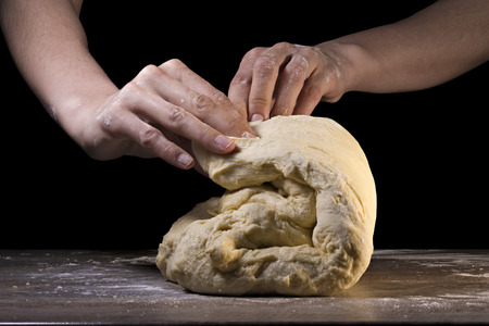 knead: Womens hands knead the dough on a black isolated background