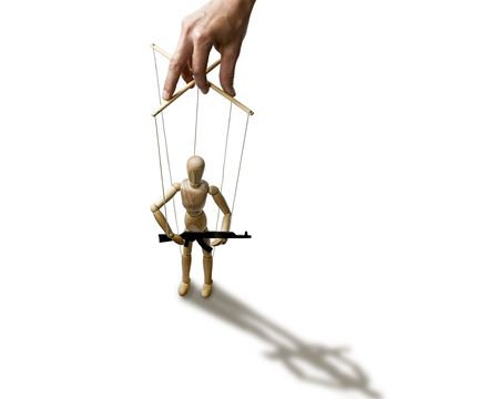 A puppet with  gun in the hands of the tyrant on the isolated white background Standard-Bild