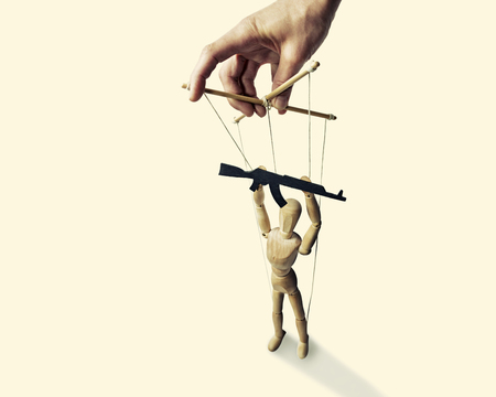 tyrant: A puppet with  gun in the hands of the tyrant on the isolated toned background Stock Photo