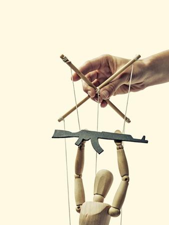 Een marionet met pistool in de handen van de tiran op de geïsoleerde afgezwakt achtergrond
