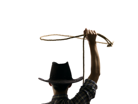 lasso: cowboy throws a lasso on the isolated background Stock Photo