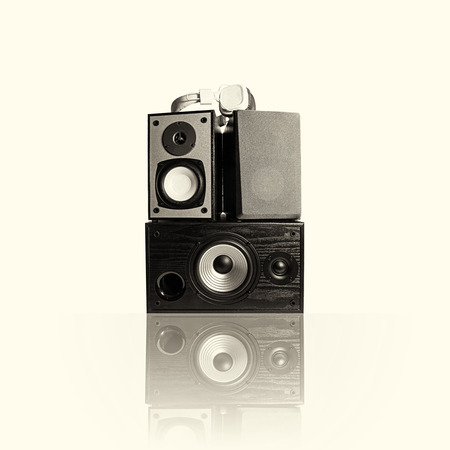 Image of three audio speakers in a wooden case and headphones. Photo black and white, toned, isolated on a light background with reflection on a horizontal surface. There is an empty seat for your text.