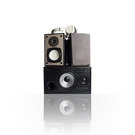 Image of three audio speakers in a wooden case and headphones. Photo isolated on white background with reflection on a horizontal surface. There is an empty seat for your text. Banco de Imagens