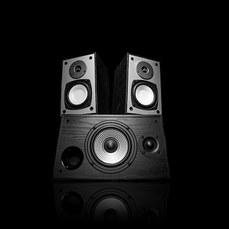 Image of three audio speakers in a wooden case. Photo black and white, isolated on a black background with reflection on a horizontal surface. There is an empty seat for your text.