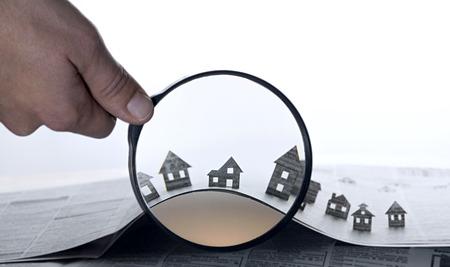 De hand houdt het vergrootglas in de voorkant van een open krant met papier huizen. Dat zou kunnen betekenen dat de huur, zoeken, kopen vastgoed. Stockfoto