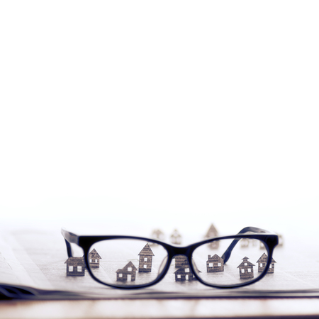 Eyeglasses lie on the open newspaper with paper houses. That could mean rent, search, purchase real estate. The template has lot of space for your text. Stock fotó