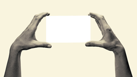 porting: Two hands holding a white, rectangular object. This toned, black and white image is isolated on light  background  for ease of porting to your design. Stock Photo