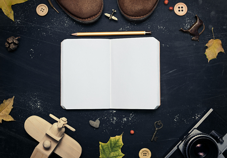 composition notebook: Composition of suede shoes, retro camera, wooden airplane, yellow leaves, notebook, pencil,  on a dark, scratched background.  In the center of an open notebook with free space for your design. Mock up for art work. Stock Photo