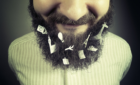 freelancing: image of a smiling bearded man. Various objects - symbols of travel, tourism, vacation pasted in his beard. The concept of freelancing, tourism, vacation, traveling on a dream