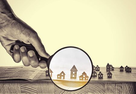Hand holds the magnifying glass in front of an open newspaper with paper houses. That could mean rent, search, purchase real estate.