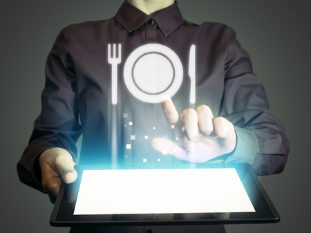 Image of a girl with tablet in her hands and food restaurant icon. She looking menus, ordering food delivery, rate restaurant with using online services.