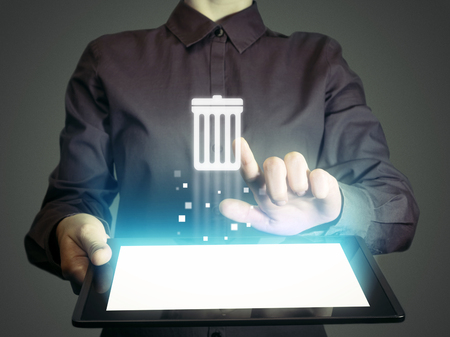 Image of a girl with tablet in her hands. She presses trash can icon. The concept of deleting files, contacts, putting in order, cleaning service etc