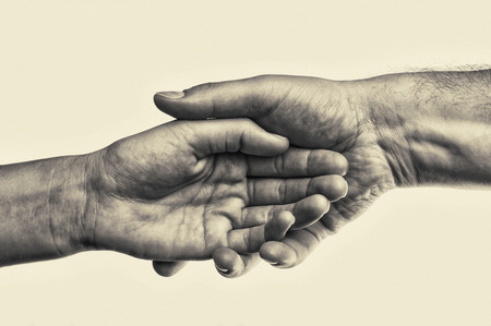 Male hand holds the female palm on toned background. That could mean help, guardianship, protection, love, care etc. This Image isolated for easy  transfer in your design.