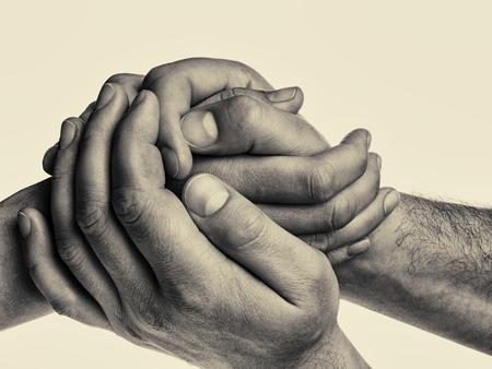De handen van mensen houden de vrouwelijke palm op geïsoleerde, gestemde achtergrond. Dat zou kunnen betekenen hulp, voogdij, bescherming, liefde, zorg, etc.
